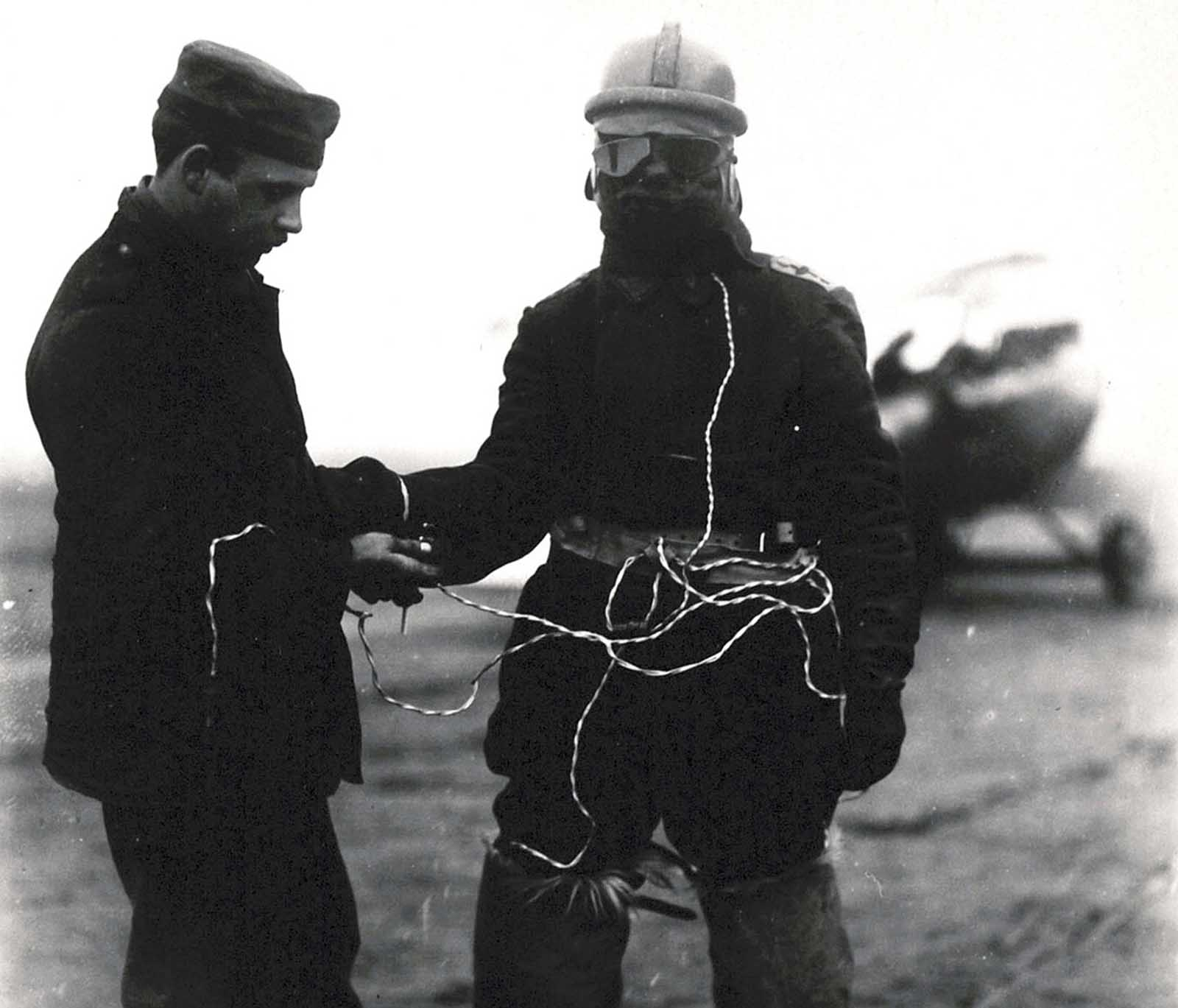 A German aviator's suit is equipped with electrically heated face mask, vest, and fur boots. Open cockpit flight meant pilots had to endure sub-freezing conditions.