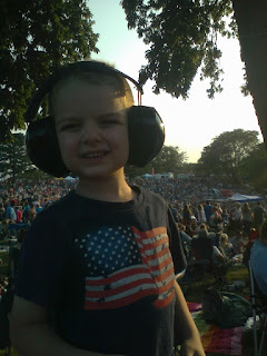 kid wearing protective headphones at Sioux City Saturday in the Park music festival