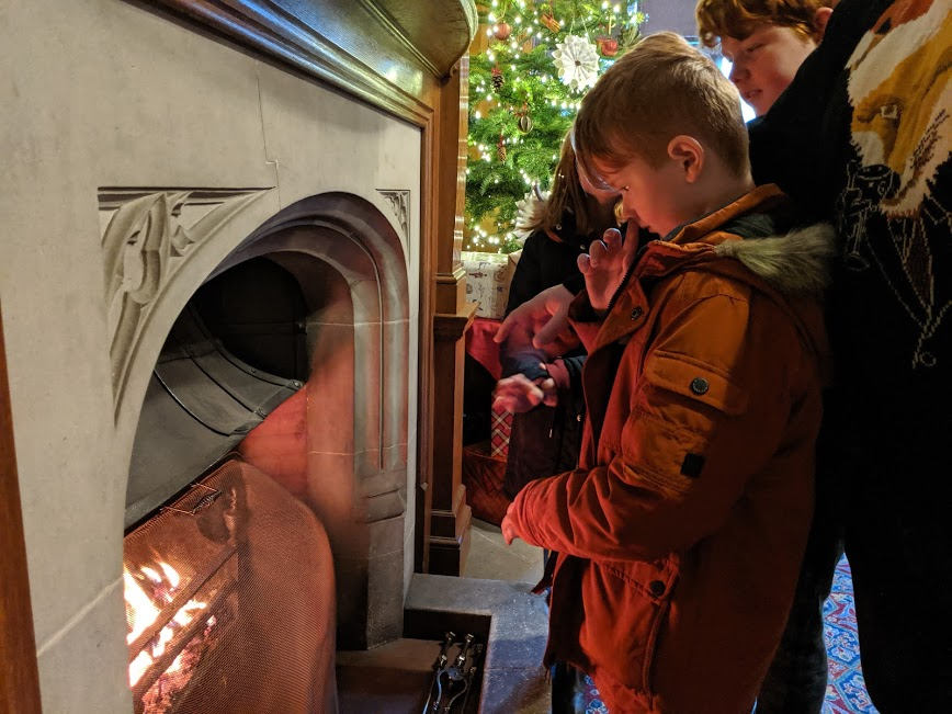 Christmas & Santa at Cragside Review  - warming hand by fire