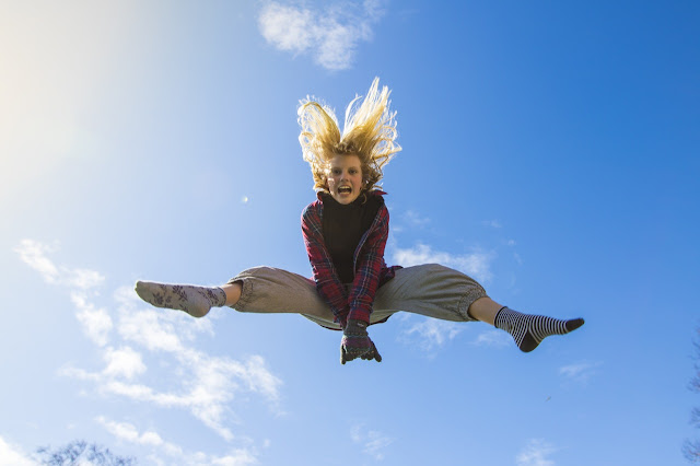 Young girl jumping in the air, looking down at you