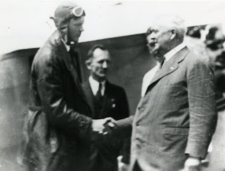 Lindbergh, wearing a pilot's flight helmet and overcoat, shakes hands with a man wearing a suit