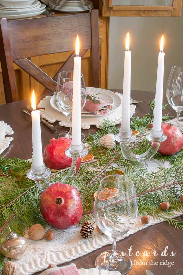 Christmas table with pomegranates, evergreen branches, vintage glass candle holders
