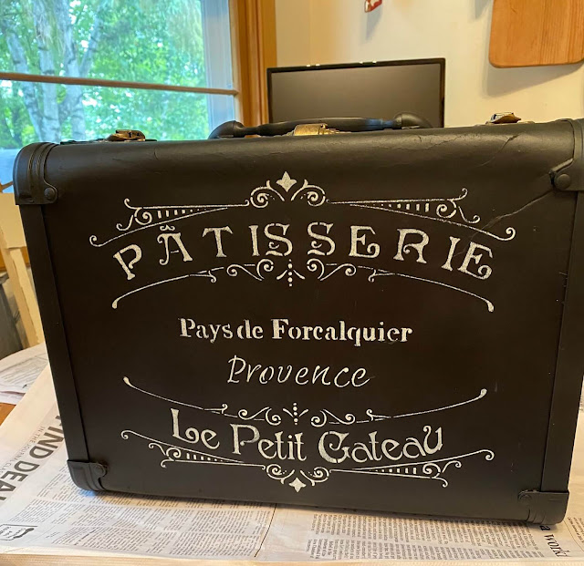 Photo of a black suitcase stenciled with a French bakery stencil