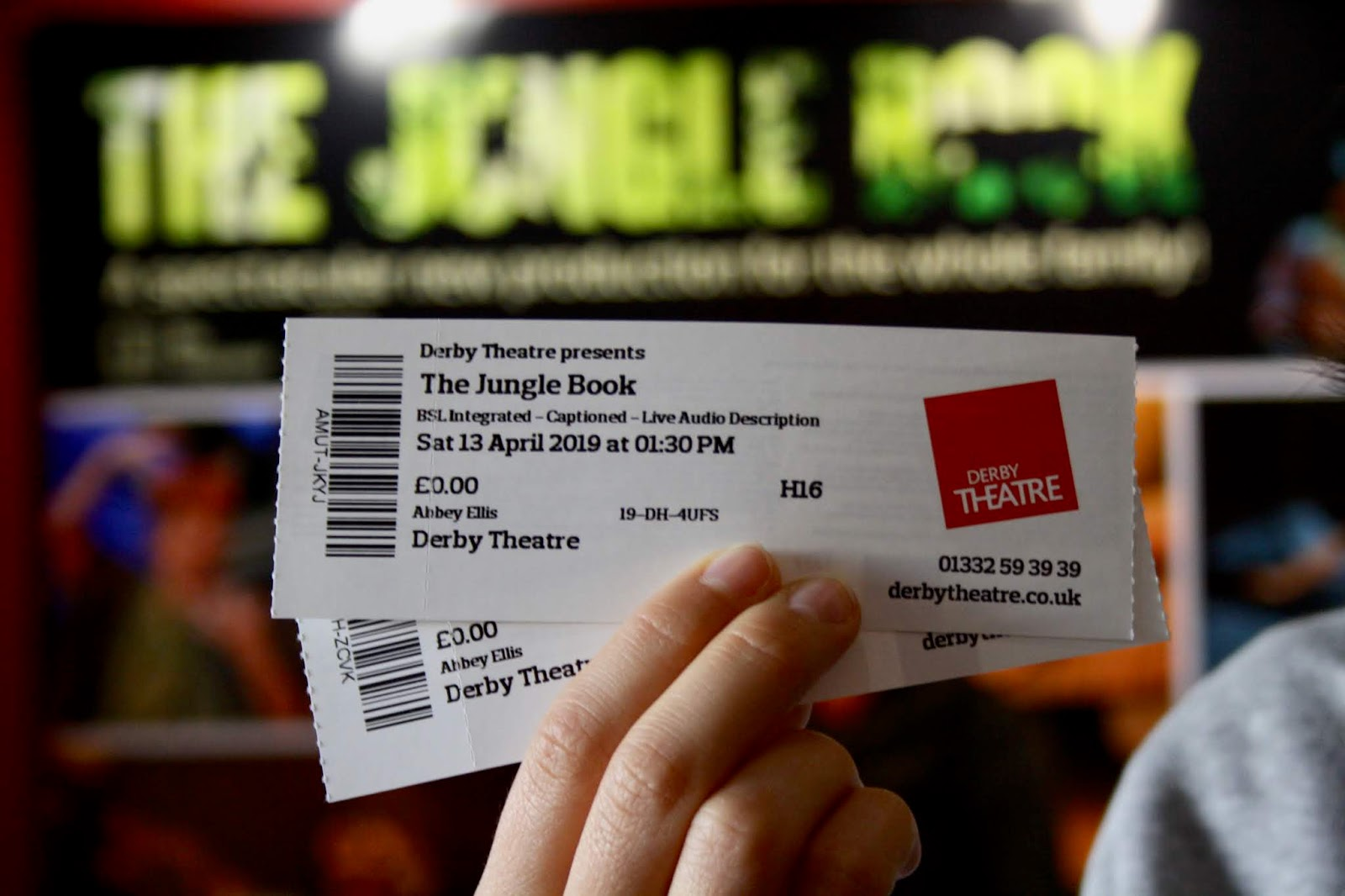 Two tickets to The Jungle Book at Derby Theatre, held up in front of a poster for the performance