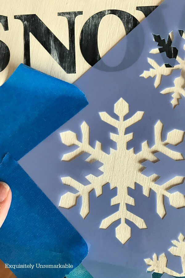 Stenciling snowflakes On Wooden board