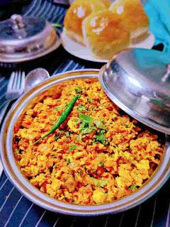 Serving egg bhurji in a serving bowl, pav in background