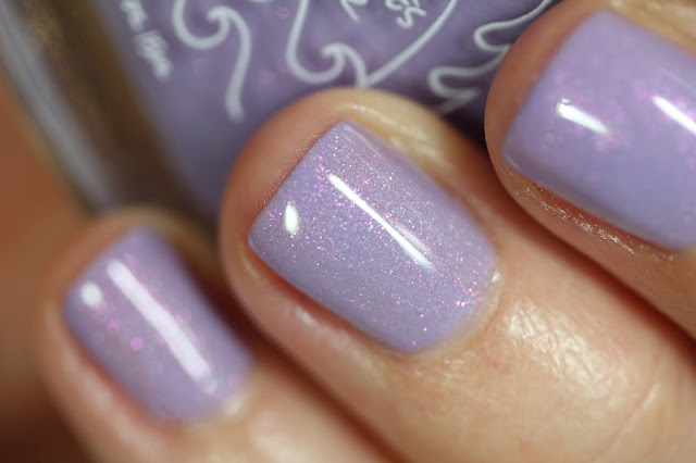 pastel lilac nail polish with green and pink shimmer shown on white person's hands