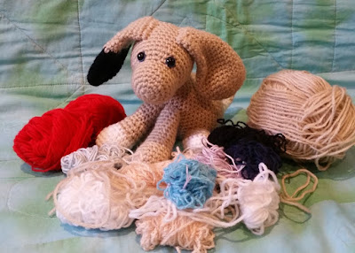 The crocheted dog is 'playing' with the scraps of yarn around it. The yarn includes 5 ply (light DK) acrylic in red and beige; 8 ply (DK) acrylic in light brown and white, 4 ply cottons in black, navy, light blue, mauve and blue-grey sparkle blend