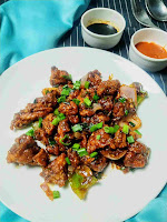 Serving chicken manchurian in a plate, soya sauce and red chilly sauce in background