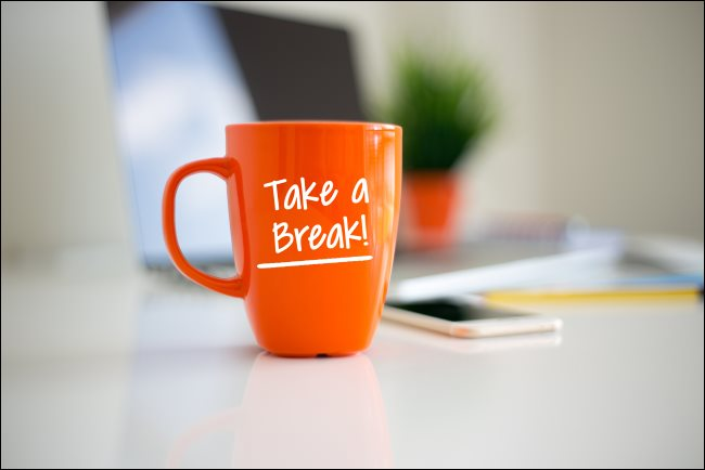 """كوب قهوة برتقالي عليه عبارة """"Take a Break!""""  مطبوعة عليها."""