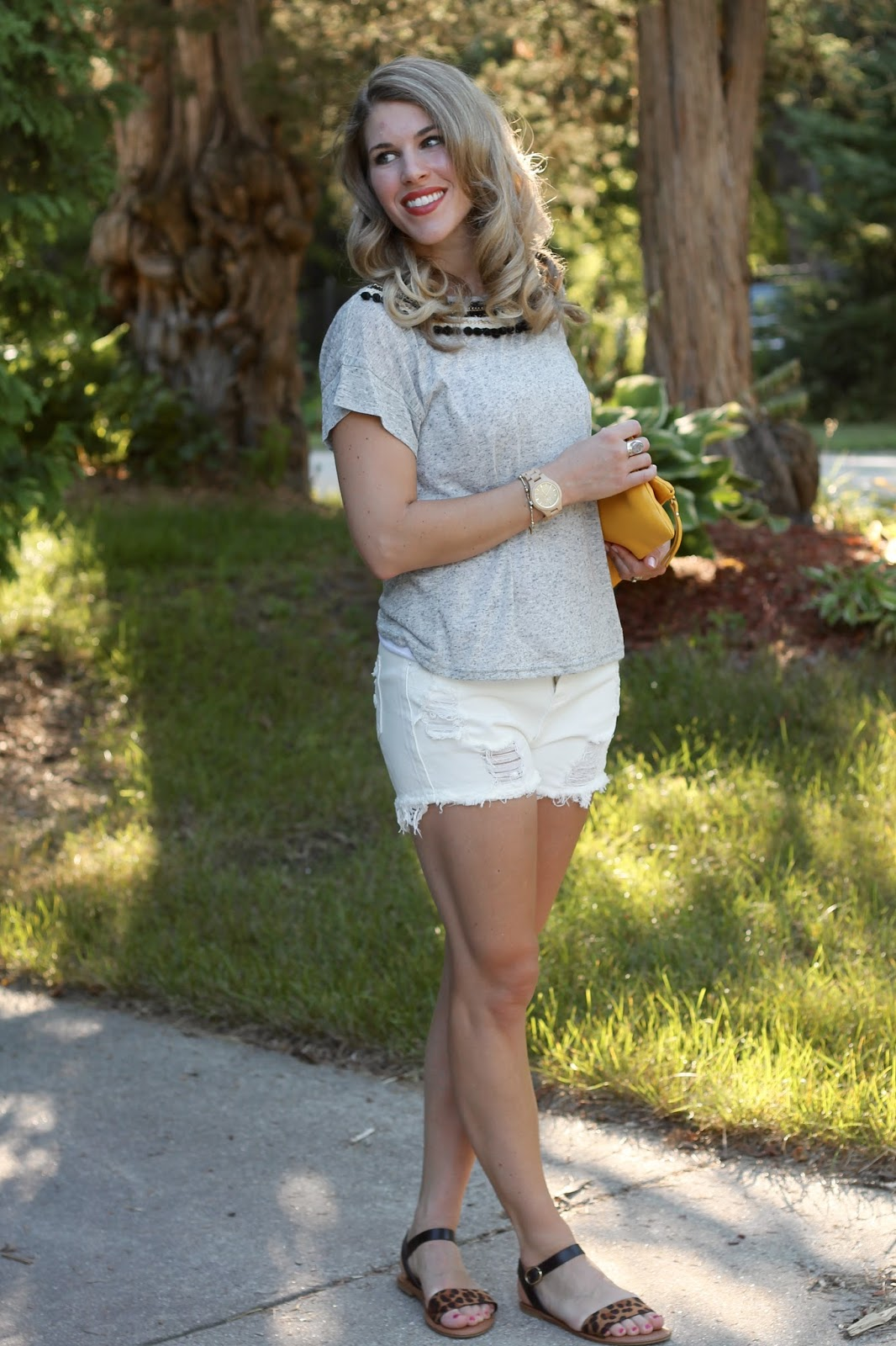 grey pom pom tee shirt, white distressed shorts, leopard sandals, yellow foldover clutch, casual summer outfit,