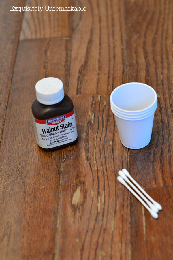 Walnut Stain Wood Stain on floor with a cup and q tips