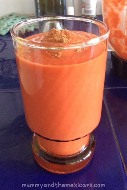 4 Ways To Eat Mamey - Image Shows Coral-Coloured Mamey Smoothie on Dark Blue Tile Background