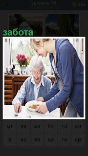 за столом пожилая женщина, о ней забота девушки подающая еду в тарелке
