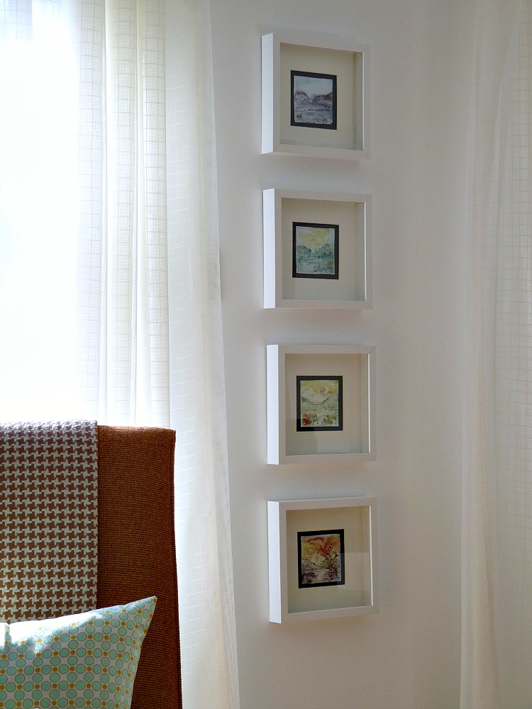 Hanging a column of art between windows