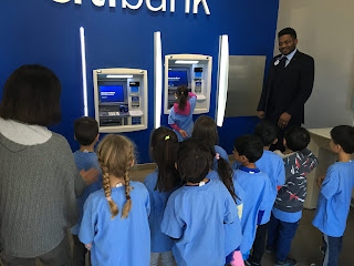 students stand near an ATM machine
