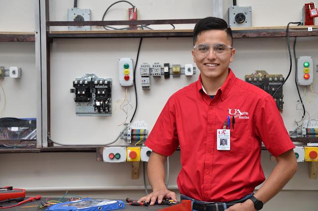 man standing in front of industrial mechanics equipment