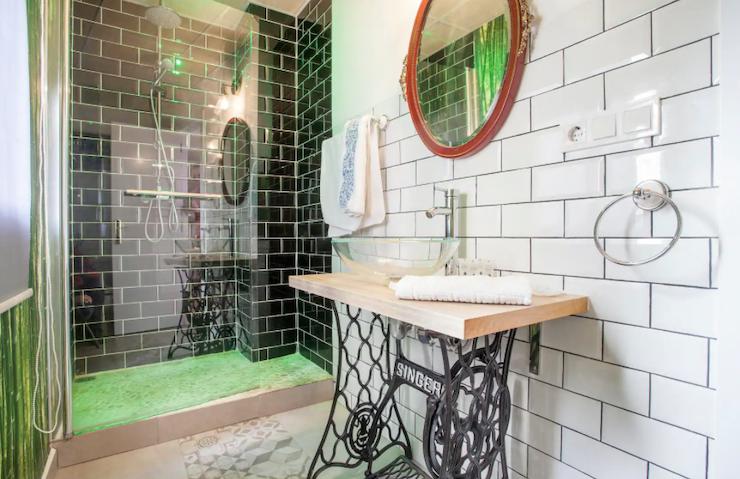 Cómo decorar una casa para alquilar: baño reformado con detalles vintage, como el pie del lavabo con la base de una máquina de coser Singer.