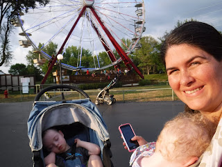 a ferris wheel is visible in the background as a woman with dark brown hair smiles and snuggles a sleeping baby in a carrier next to a blue stroller where a blonde boy is also sleeping
