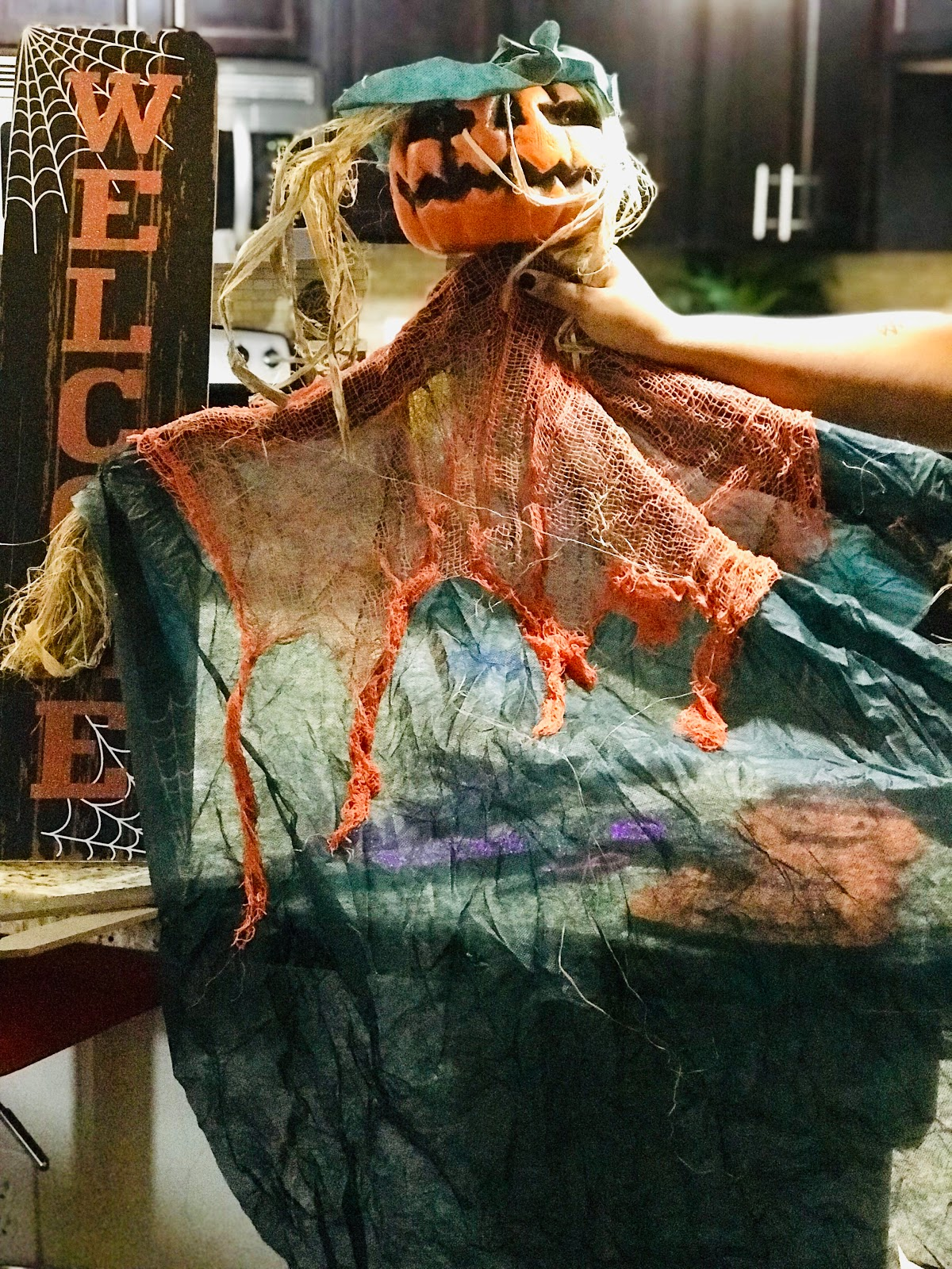 Image: Woman holding up pumpkin ghost head from Dollar Tree. That will be used as decor for Halloween. Seen first on Bits and Babbles Blog
