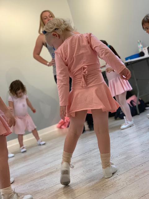 A 3 year old in pink ballet clothes and white tap shoes