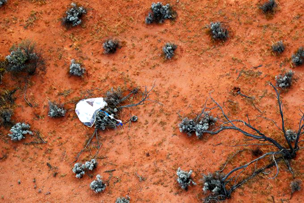 Hayabusa2's sample return capsule, with its parachute still attached, lies on the ground at the landing site in Woomera, Australia...on December 6, 2020 (Japan Time).
