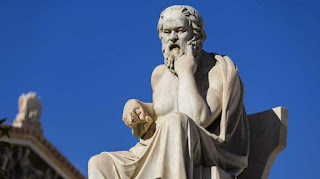 Here we have an image of a statue of Socrates sitting in a chair. He is leaning slightly forward with his left hand up to his face. The expression on his face is one of deep thought and contemplation.