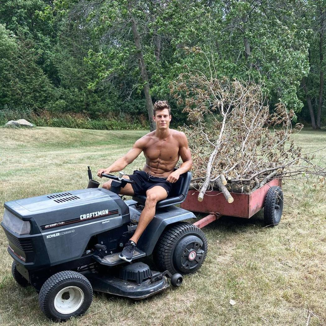 young-shirtless-fit-worker-driving-mini-tractor