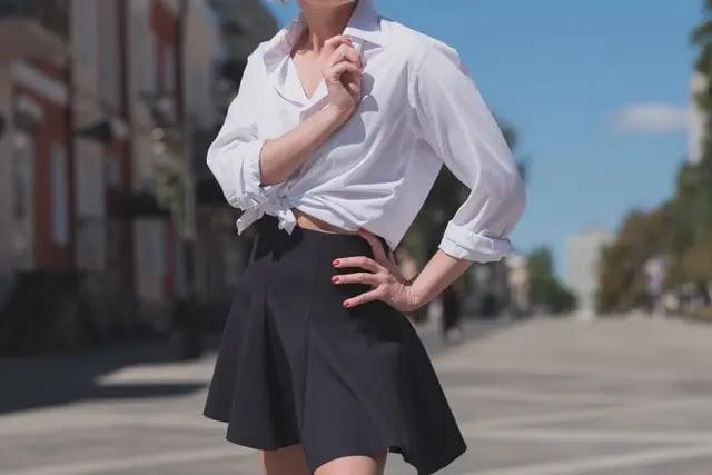 Mujer con blusa blanca y falda negra en la calle