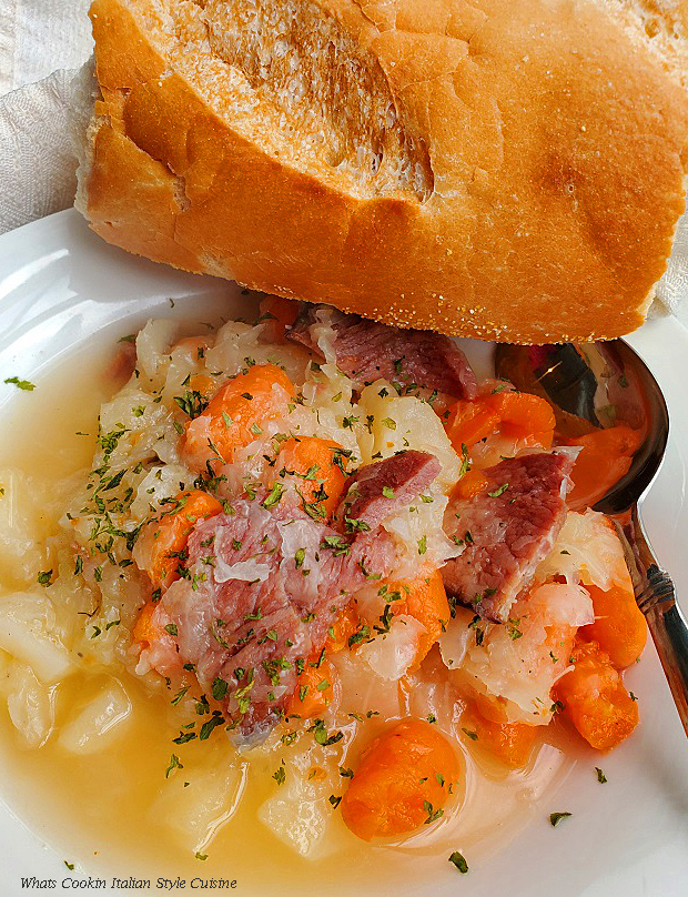 this is a bowl of cabbage and ham with potatoes and carrots in a white bowl with a hunk of Italian bread on the bowl