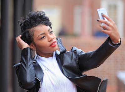 Pretty young black woman taking selfie