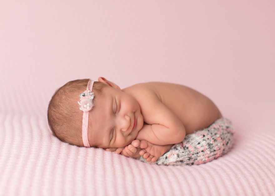 the photographer catches the smiles of sleeping babies