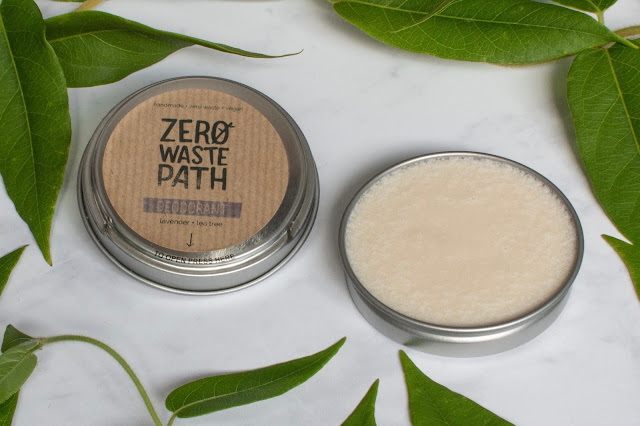Tin of deodorant open to show the cream inside and surrounded by leaves