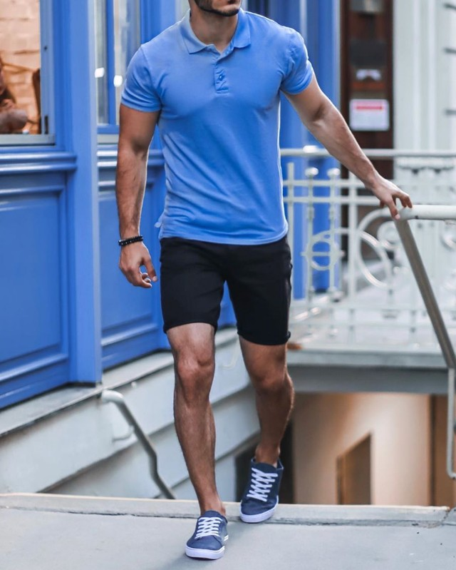 A man in blue polo t-shirts and black shorts.