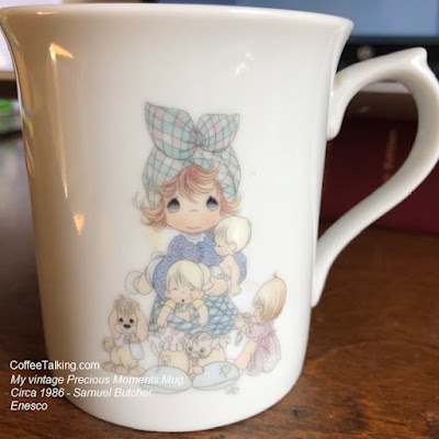 It's a Precious Moments by Samuel Butcher (of course) and it was branded Enesco Gifts - and is part of a calendar set available in 1986.