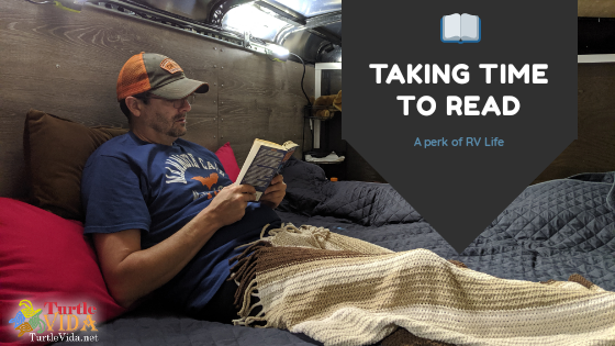 Man sitting on a bed reading a book | Taking Time to Read | A Perk of RV Life