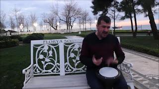 Fotografía de Bilal tocando el tambor sentado un banco blanco