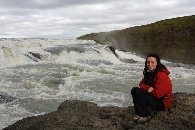 Lena al lado de la corriente de río Hvítá, en la cascada de Gullfoss