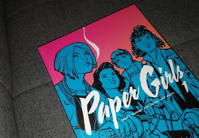Comics Paper Girls posé sur un canapé gris