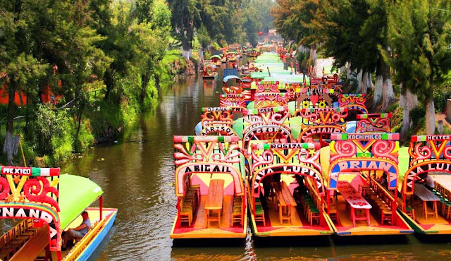 Las coloridas, floreadas y muy adornadas trajineras son uno de los rasgos distintivos de este popular e importante lugar de la cultura mexicana, donde aún se cultiva en chinampas, los campesinos se trasladan navegando a través de los canales y se mantienen vivas sus fiestas y celebraciones.