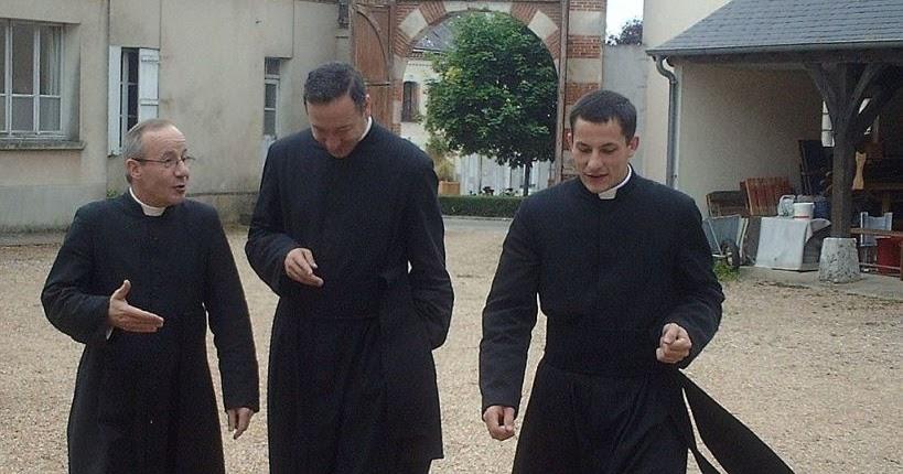 Uomini in giacca e cravatta sorridono con un sacerdote all