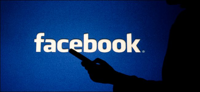شخصية غامضة تستخدم هاتفًا ذكيًا أمام شعار Facebook.