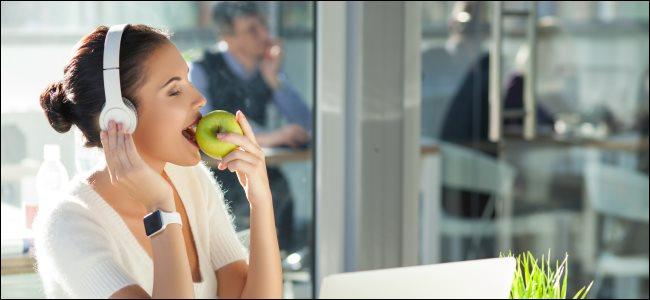 امرأة ترتدي سماعات الرأس أثناء استخدام Apple Watch وتناول تفاحة.