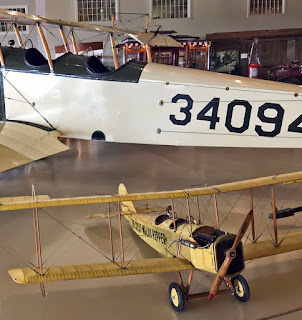 Airplane on museum floor is a model next to the real thing.