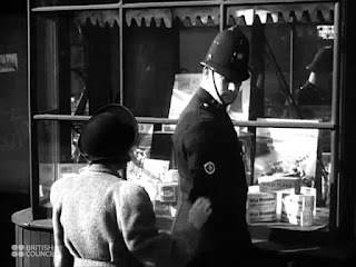 Black and white film still showing a young woman in a hat tapping on the shoulder of a policeman in 1940s English PC uniform. They are standing outside a shop window.