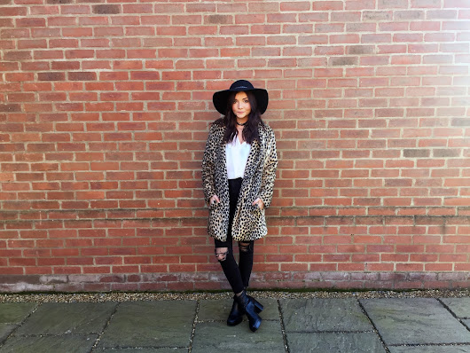Leopard fur coat styled with ripped jeans, a hat and fishnets