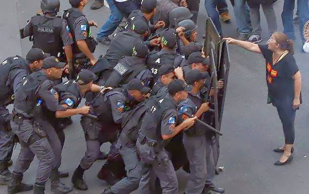 A CORAGEM DESTA PROFESSORA É UM SIMBOLO DE RESISTÊNCIA A TRUCULÊNCIA DE POLICIAIS ARMADOS.