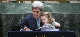 المبعوث الأميركي الخاص لشؤون المناخ، جون كيري، يوقع اتفاق باريس في عام 2016، ومعه حفيدته