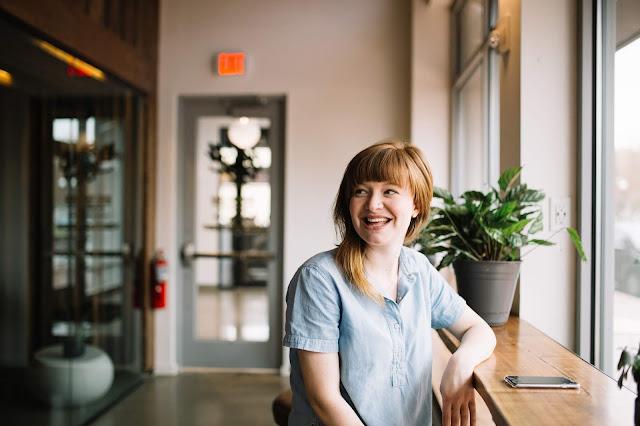Mulher loira sentada sorrindo no escritório