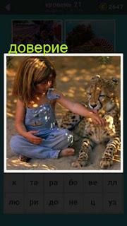 ребенок на земле сидит и играет с маленьким леопардом 21 уровень 667 слов